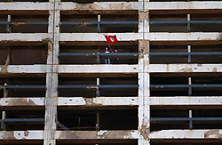 Two demonstrators wave a flag from the top of the Holiday Inn, a landmark of serious fighting from the days of the civil war, Beirut, Lebanon, Feb. 21, 2005. Several thousand Lebanese gathered at the scene of the bombing that killed former Prime Minister Rafik Hariri, afterward they walked to his grave. The crowd demanded a Syrian pullout and an international probe into the assassination.