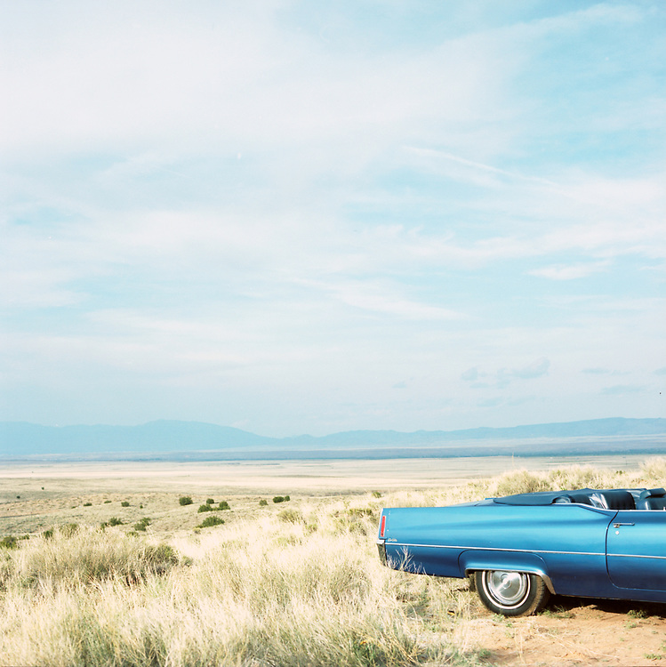 Partial view of vintage blue convertible parked in the desert plains of New Mexico.
