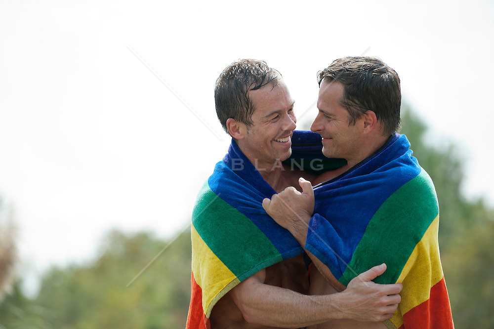 gay male couple wrapped in a rainbow towel looking at each other