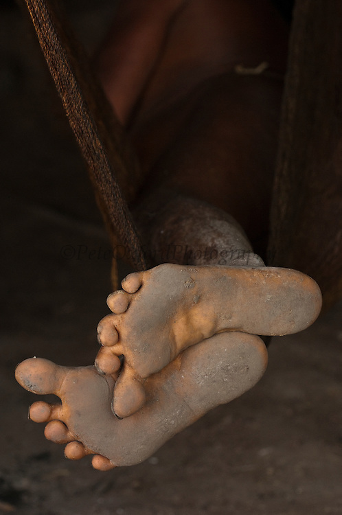 Huaorani Indian - Megatowe Ontogamo's feet while lying in his hammock. Gabaro Community. Yasuni National Park.<br /> Amazon rainforest, ECUADOR.  South America<br /> This Indian tribe were basically uncontacted until 1956 when missionaries from the Summer Institute of Linguistics made contact with them. However there are still some groups from the tribe that remain uncontacted.  They are known as the Tagaeri and Taramanani. Traditionally these Indians were very hostile and killed many people who tried to enter into their territory. Their territory is in the Yasuni National Park which is now also being exploited for oil.