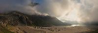 Summit of Storskiva mountain peak emerges from fog at Bunes beach, Moskenesøy, Lofoten Islands, Norway