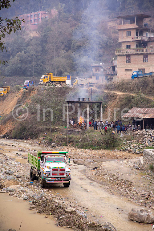A truck driving along  the Nakkhu river bed past the cremation of a local man taking place at Tikabhairab Temple on the 13th of March 2020 in Tikabhairab, Lalitpur, Kathmandu District, Bagmati Pradesh, Nepal.
