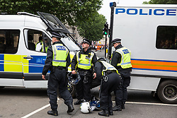 London, UK. 9th June, 2018. Metropolitan Police officers prepare riot gear in a sterile area created in Parliament Street between the far-right March for Tommy Robinson and anti-fascists holding a counter-protest.