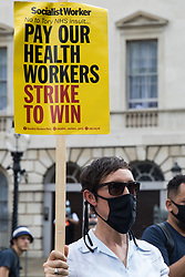 London, UK. 20th July, 2021. A campaigner holds a placard in support of NHS workers from the grassroots NHSPay15 campaign meeting outside Parliament before marching to 10 Downing Street to present a petition signed by over 800,000 people calling for a 15% pay rise for NHS workers. At the time of presentation of the petition, the government was believed to be preparing to offer NHS workers a 3% pay rise in 'recognition of the unique impact of the pandemic on the NHS'.