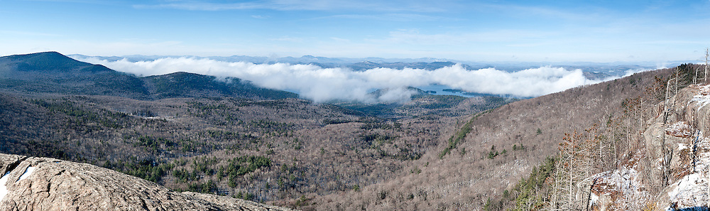 Lake George, Adirondacks, NY.<br /> <br /> I had a splitting headache from painting in my home; I needed a day out getting fresh air into me.  I didn't really plan on climbing Sleeping Beauty, it just kind of evolved as I drove northward.  The mountain is mainly a forest trail,following stream beds to the top, now frozen, and hazardous if not for micro spikes.  Until I began generating some hiking heat, it became damnably cold as those first few hikes of winter in single digit mornings tend to be.  By the way, it always helps to curse the cold, although I suppose an apology was in order upon reaching the summit and beholding the site below me.  A marine layer covered the length of the lake, as yet unaffected by the low trajectory of the sun.  The resultant convection cloud shifted and curled over the the lower ridges along the shore, pluming upwards and breaking off, at times, to reveal lake and islands at the valley's bottom.  I perched on a cliff top and waited out periods of total obscurity for moments like these--peeks into the Lake George basin, delineating the watershed dropping off the slopes below me and the ridge lines of ranges fading westward.  I was treated to the spectacle for a good half an hour, the sun finally reaching enough strength to burn it off.  I realized that I had forgotten just how cold I was as my fingers fumbled folding up my tripod;  leaving, another hiker trudged out of the woods to the summit ledges and I gave greeting, but didn't mention the hang time I shared, now gone and indescribable.