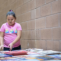 On Thursday in Twin Lakes, Bridgette Barney, 7, lays out books for everyone to borrow during the Family Math Night held at Twin Lakes Elementary School.