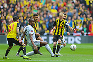 Wolverhampton Wanderers defender Willy Boly (15) performs a tackle on Watford midfielder Will Hughes (19) during the The FA Cup semi-final match between Watford and Wolverhampton Wanderers at Wembley Stadium, London, England on 7 April 2019.