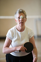 Shot of an older woman playing table tennis,