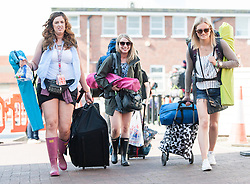 © Licensed to London News Pictures. 11/06/2015. East Cowes, UK.  Festival goers in shorts and wellies travelling to Isle of Wight Festival 2015 get off the Southampton-East Cowes ferry early on thursday morning.  This years festival include headline artists the Prodigy, Blur and Fleetwood Mac.  Photo credit : Richard Isaac/LNP