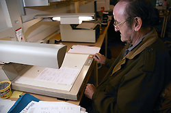 Man with disability working as microfilm technician; operating equipment in visual communications office,