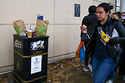 © Licensed to London News Pictures. 08/11/2020. London, UK. Women walk past an overflowing bin. Restaurants are currently only providing take away services due to the second coronavirus lockdown, which is resulting in bins overflowing outside shops in Haringey Arena Shopping Park, north London. The lockdown will last until Wednesday 2 December, to control the increase of coronavirus cases. Photo credit: Dinendra Haria/LNP