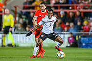 Trinidad and Tobago midfielder Cordell Cato shields the ball from Wales defender Neil Taylor during the Friendly European Championship warm up match between Wales and Trinidad and Tobago at the Racecourse Ground, Wrexham, United Kingdom on 20 March 2019.