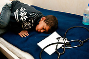 Greece with Doctors of the World (Medecins du monde). Hellenic Seaways ferry from Lesvos to Chios to Athens, taken by refugees. Doctors of the World have a clinic on board with a doctor, nurse, interpreters and social workers. An exhausted child falls asleep on the examining couch in the clinic cabin.