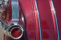 Red tail light matches red car body, offset with chrome detail