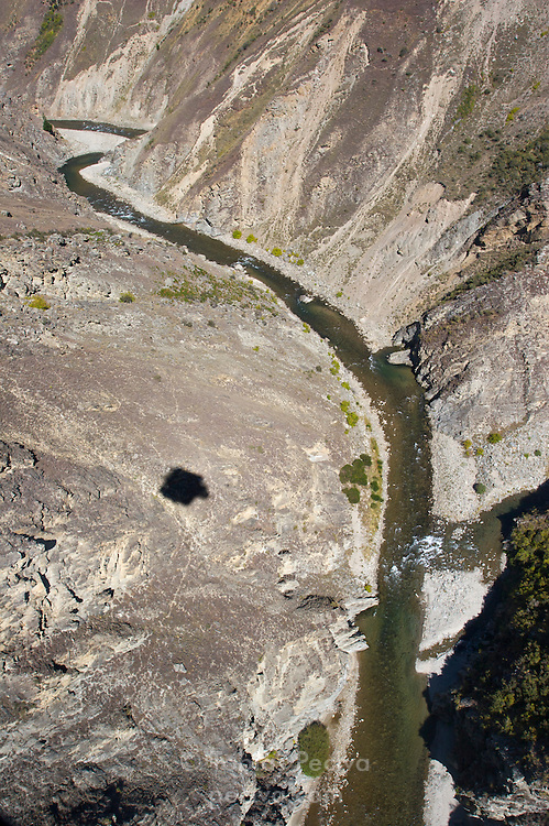 Nevis Gorge and the Nevis River, near Queenstown, New Zealand. The shadow of the Nevis Highwire bungy jump pod is visible. The pod is suspended 134m (440ft) above the river.