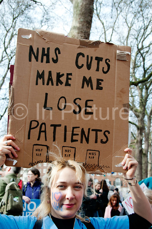 Tens of thousands of health workers, activists and members of the public protested against austerity and cuts in the NHS National Health Service on March 4th 2017 in London, United Kingdom. A young woman healthworker, with a NHS heart on her cheek, holds a sign saying NHS cuts make me lose patients,