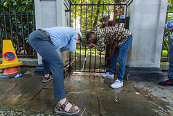 © Licensed to London News Pictures. 07/09/2021. London, UK. Pro Afghanistan demonstrators protesting outside the Pakistan High Commission take cold hose pipe water from a gardener to cool off from the 29C mini heatwave hot weather. Photo credit: Ray Tang/LNP