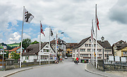 Adlerplatz is the heart of Appenzell village, in Switzerland, Europe. Metzibrücke bridge crosses Sitter river. Yellow shutters mark Hotel Cafe Adler. Most of the notable buildings in Appenzell were built in the 1500s. Appenzell Innerrhoden is Switzerland's most traditional and smallest-population canton (second smallest by area).