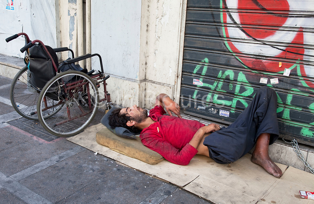 Severley disabled man sleeping beside his wheelchair on the streets against a graffitied wall. Disadvantaged people on the streets in the area of Omonia. Just moments after these pictures were taken, a junkie came up and stole a 1 Euro coin from the sleeping mans hand. A clear sign of the desperation on the streets here. In this area the amount of ill, disabled, badly injured, or sick people either begging or sleeping on the streets is staggering. The area has been taken over by drug dealers, homeless people, and prostitution. Athens is the capital and largest city of Greece. It dominates the Attica periphery and is one of the world's oldest cities, as its recorded history spans around 3,400 years. Classical Athens was a powerful city-state. A centre for the arts, learning and philosophy.