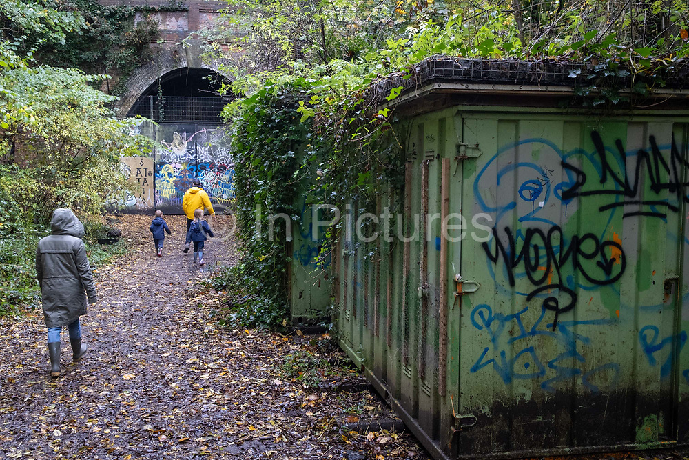 A family walk towards the closed tunnel that was once part of the Nunhead to Crystal Palace (High Level) railway which once passed through Sydenham Hill Woods. The track bed can be followed to a disused and closed tunnel which is now a registered bat roost, on 25th October 2020, in London, England.