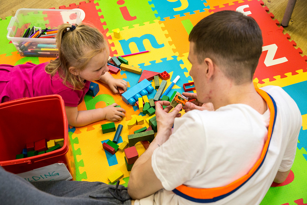 A young father bonding with his baby daughter in the children's play area during a family visit in HMP Brixton, South London on the 26th of July 2016, London United Kingdom. The Prisoner Advice & Care Trust (PACT) organise special family days that help the men inside the prison connect with and support their partners and children on the outside. (photo by Andy Aitchison)