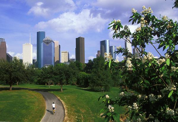 Stock photo of a cyclist riding down a path on the Buffalo Bayou Hike and Bike Trail near downtown Houston Texas