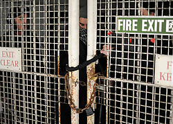 © Licensed to London News Pictures. 21/01/2012, London, UK. Protesters on the inside of the building lock a gate. Occupy London protesters this morning publicly repossessed Roman House, an abandoned nine-storey office building in the Barbican. The Occupy London campaigners - part of the global movement for social and economic justice and real democracy - stated that they intend to occupy the building - their fifth occupation - until such time as the City of London Corporation publishes full details of its City Cash Accounts.  Photo credit : Stephen Simpson/LNP