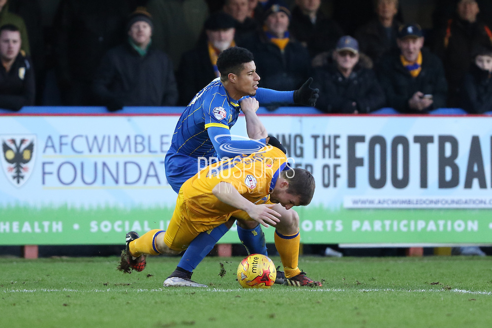 Lyle Taylor of AFC Wimbledon and Jamie McGuire of Mansfield Town tussles during the Sky Bet League 2 match between AFC Wimbledon and Mansfield Town at the Cherry Red Records Stadium, Kingston, England on 16 January 2016. Photo by Stuart Butcher.