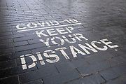 As the third national coronavirus lockdown continues, one of the many Covid-19 keep your distance signs painted onto the pavements in the City Centre on 18th January 2021 in Birmingham, United Kingdom. Following the recent surge in cases including the new variant of Covid-19, this nationwide lockdown, which is an effective Tier Five, advises all citizens to follow the message to stay at home, protect the NHS and save lives.