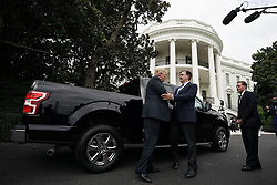 "WASHINGTON, DC - JULY 23: U.S. President Donald Trump (L) talks to Ford Motor Company Vice President of U.S. Government Relations Curt Magleby (2nd L) in front of an F-150 pick up truck during the 2018 Made in America Product Showcase July 23, 2018 at the White House in Washington, DC. The White House held the showcase to ""celebrates every state's effort and commitment to American-made products, and will allow these companies to speak with senior Administration officials, including the President, the Vice President, members of the Cabinet, and senior staff."" (Photo by Alex Wong/Getty Images)"