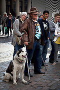 Man with his dog watches a street performance. Covent Garden in the West End of London.