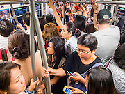 """22 MAY 2014 - BANGKOK, THAILAND: Thais crowd onto the BTS Skytrain after work to get home before a curfew goes into effect. The Thai army suspended civilian rule, suspended the constitution and declared the """"military takeover of the nation."""" The announcement came just before evening as a meeting between civilian politicians and the army was breaking up with no progress towards resolving the country's political impasse. Civilian politicians were arrested when the meeting ended. The army also declared a curfew from 10PM until 5AM.    PHOTO BY JACK KURTZ"""