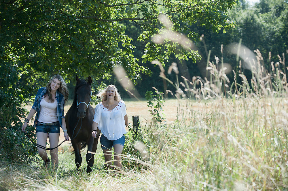 Two women walking with a horse on meadow and smiling, Bavaria, Germany