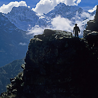 A Peruvian villager treks a rugged trail towards Victoria Pass in the rugged Cordillera Vilcabamba of Peru's Andes mountains.  Behind him are the crags and glaciers of Nevado Sacsarayoc.