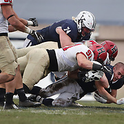 NEW HAVEN, CONNECTICUT - NOVEMBER 18: Running back Zane Dudek #33 of Yale loses his helmet as he is tackled by Tristan Tahmaseb #91 of Harvard and Scott Garrison #74 of Harvard during the Yale V Harvard, Ivy League Football match at the Yale Bowl. Yale won the game 24-3 to win their first outright league title since 1980. The game was the 134th meeting between Harvard and Yale, a historic rivalry that dates back to 1875. New Haven, Connecticut. 18th November 2017. (Photo by Tim Clayton/Corbis via Getty Images)