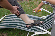 Applying aerosol spray of Mosquito repellent to bare ankle. Zawady Central Poland