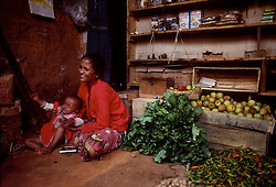 POKHARA, NEPAL - OCTOBER 1992 - A woman tends to her child at her home where she sells produce and other goods in Pokhara Nepal. (PHOTO © JOCK FISTICK)