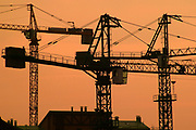 silhouette of construction crane on the background of orange sunset
