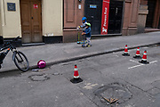 Two boys scoot past a split pink plastic sphere which has come to rest in the gutter on a side street in central London, on 23rd February 2021, in London, England.