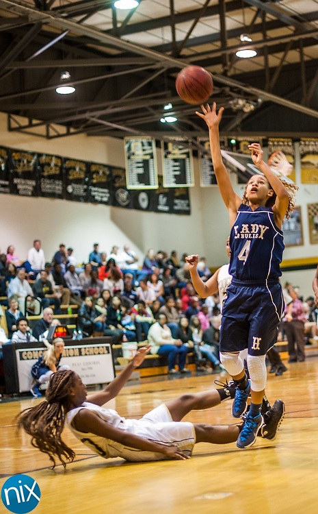 Hickory Ridge's Stacia Means takes a shot after Concord's Jessica Williams is knocked down Friday night at Concord High School. Hickory Ridge won the game 55-35.