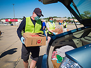 29 MAY 2020 - DES MOINES, IOWA: A volunteer loads a box of produce into a car during a produce distribution in a mall parking lot in Des Moines. The Des Moines Area Religious Council (DMARC) and Capitol City Fruit from Norwalk, IA, gave away 1,800 boxes of fresh produce with a mix of vegetables and fruit. The boxes contain enough produce to feed a family of four for a week. The produce was provided by the USDA Farmers to a Families food program. Because of the COVID-19 pandemic, the unemployment rate in Iowa hit 10.2% in May, the highest unemployment rate ever recorded in Iowa and food insecurity in Iowa is impacting communities throughout the state.          PHOTO BY JACK KURTZ