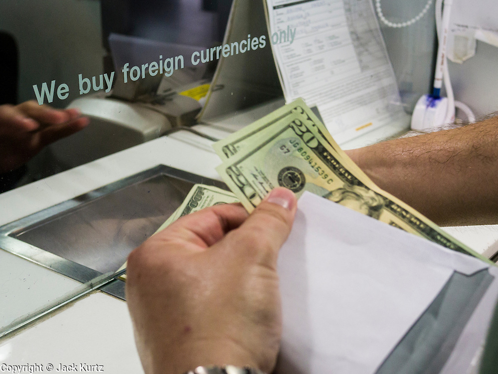 22 APRIL 2013 - BANGKOK, THAILAND:  A European tourist buys Thai Baht at a foreign currency exchange kiosk in Bangkok. The Thai Baht has gained markedly against the US Dollar, the Euro and Pound Sterling in recent months. On Monday, the Baht was trading at 28.57 Baht to 1 US Dollar on Apr. 22. The strengthening Baht means imported goods are cheaper in Thailand, but Thai exports cost more in other countries. It also means tourists and expats who live in Thailand have less money to spend as their currencies buy fewer Baht. The baht has risen 5 percent against the dollar this year to its highest level since before the Asian financial crisis in 1997. The Federation of Thai Industries, which has led calls for the authorities to act to lower the baht, said the rise in the past two weeks had been too rapid and its members were finding it hard to cope with the volatility because as the Baht appreciates their exports become more expensive. Thailand is among the world's leading exporters of rice, chicken, pork, electrical components, cars and is the leading exporter of canned tuna.   PHOTO BY JACK KURTZ
