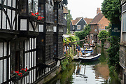 River scene with teople taking a ride on a punt in Canterbury, England, United Kingdom. Canterbury, a cathedral city in southeast England, was a pilgrimage site in the Middle Ages. Ancient walls, originally built by the Romans, encircle its medieval centre with cobbled streets and timber-framed houses. Canterbury Cathedral, founded 597 A.D. is the headquarters of the Church of England and Anglican Communion.