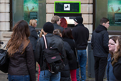 "© Licensed to London News Pictures. 7/12/2013. Lincoln, UK. Lincoln City Centre was packed with Christmas shoppers this weekend. Pictured, one of the many queues at a cash machine in the centre of Lincoln. Thousands of shoppers filled the City Centre and stewards were called in to direct people up the narrow ""Steep Hill"" towards the upper area of Lincoln near the Cathedral. Photo credit : Dave Warren/LNP"