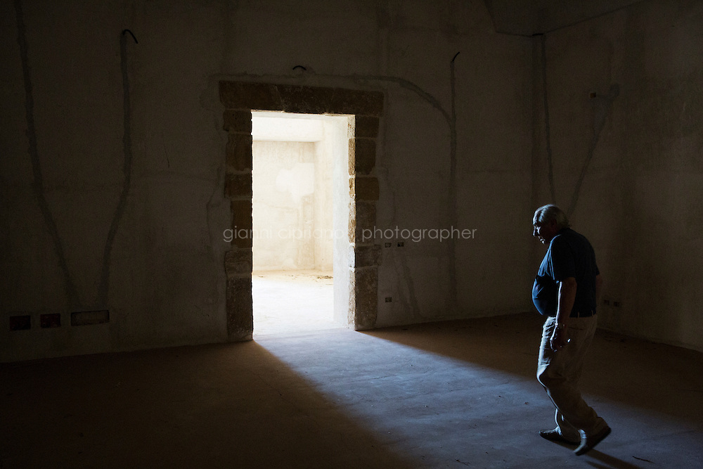 """CASTELVETRANO, ITALY - 29 MAY 2015: Antiquities dealer and olive oil producer Gianfranco Becchina (76) walks inside Palazzo Aragona Pignatelli, a XIII century palace he bought in Castelvetrano, Sicily, Italy, on May 29th 2015.<br /> <br /> Gianfranco Becchina is an Italian antiquities dealer who was taken to trial in Italy of illegally dealing in antiquities. Gianfranco Becchina dealing antiquities in Basel, Switzerland, in the 1970s, and has sold material to major museums including the Louvre, the Boston Museum of Fine Arts, the Metropolitan Museum, the Princeton University Art Museum and the J. Paul Getty Museum. Mr Becchina claims to have stopped dealing ancient art in 1994. Since 1989 he produces the olive oil """"Olio Verde"""" in Tenuta Pignatelli, his estate in the heart of the Valle del Belice, Sicily, where the Nocellara del Belice olive is grown."""
