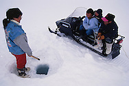 Inuit children ice fishing with their mother, Pond Inlet, Baffin island, Nunavut, Canada.