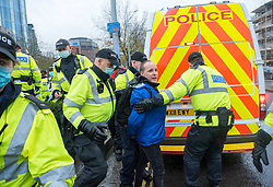© Licensed to London News Pictures; 14/11/2020; Bristol, UK. Police arrest a man in a wig which is removed by officers at an Anti-Lockdown protest march and rally by Stand Up Bristol and StandUpX2, against the Covid-19 lockdown during the coronavirus pandemic, taking place on College Green and in Bristol city centre. Protests have been declared illegal under the current Covid-19 lockdown as people are not allowed to meet in more than groups of two and police have threatened arrests and fines against those attending. Police arrested several people. The protest is against Lockdowns, Isolation of the Elderly, Ruined Childhoods, Business Closures, Masks, Government Interference in Private Life and is part of a series of protests today in Sheffield, Wolverhampton, Portsmouth, Bristol and Bournemouth. England is under a national lockdown, sometimes known as lockdown 2.0, as the UK Government tries to stop the spread of the covid-19 coronavirus pandemic. From 05 November lockdown restrictions came into force across England with all pubs, bars, restaurants and entertainment venues shut as well as all non-essential shops. People have been told to stay at home except for work, education, exercise or essential shopping and each person can only meet one other person from outside their household in an outdoors public space. Photo credit: Simon Chapman/LNP.
