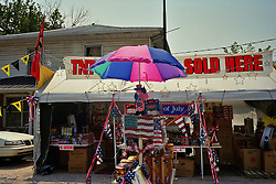 """An impromptu tent sits along the roadside in Kentucky advertising fireworks and Independence Day decorations for sale. A """"no smoking"""" sign is posted on one of the tables."""