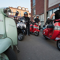 MILAN, ITALY - JUNE 05: Participants walk past a Lambretta before the start of the Vespa race on June 5, 2010 in Milan, Italy. Vespa is one of the best known Italian icons, the special Vespa weekend is the XV edition of the famous  500km night race  (Photo by Marco Secchi/Getty Images)