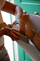 Woman's hands unpacking flat pack furniture